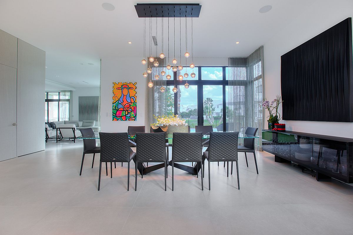 Phòng ăn tối giản tuyệt đẹp với tác phẩm nghệ thuật treo tường đầy màu sắc trong phông nền và đèn chùm xếp tầng