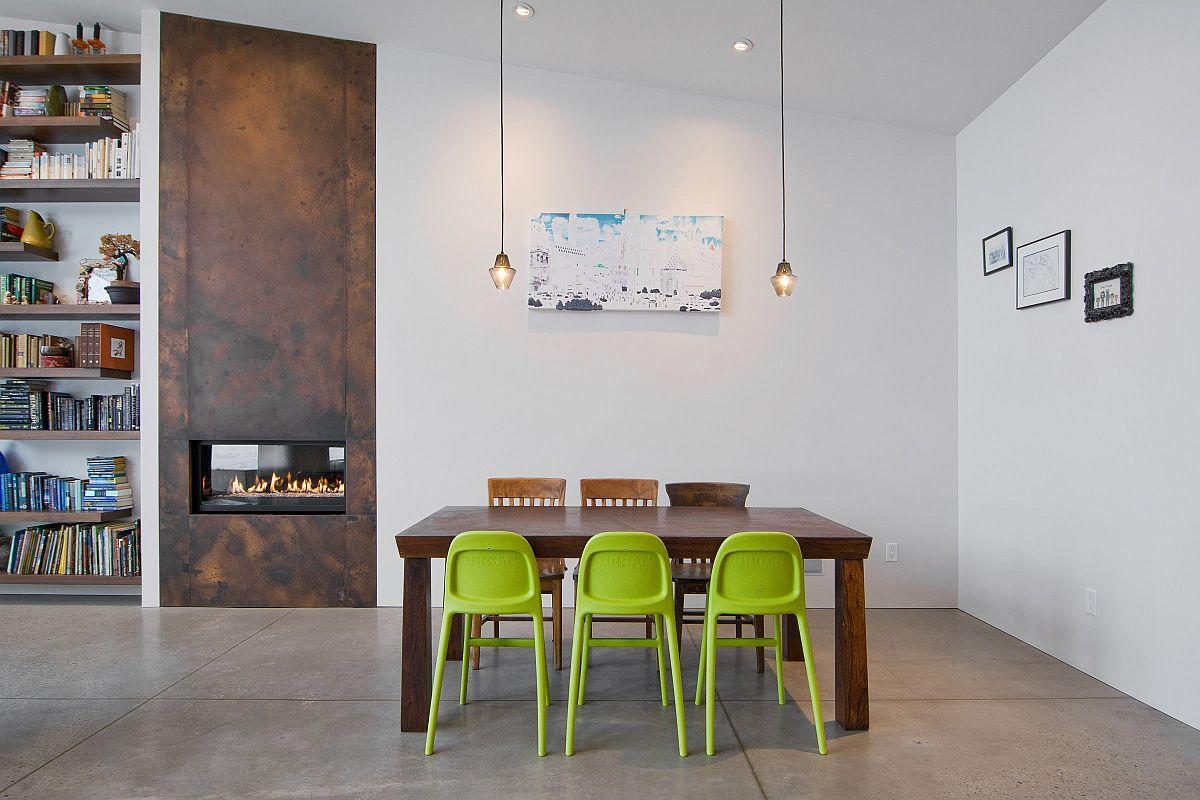Bộ ba ghế màu xanh lá cây mang lại màu sắc cho phòng ăn tối giản tinh tế này