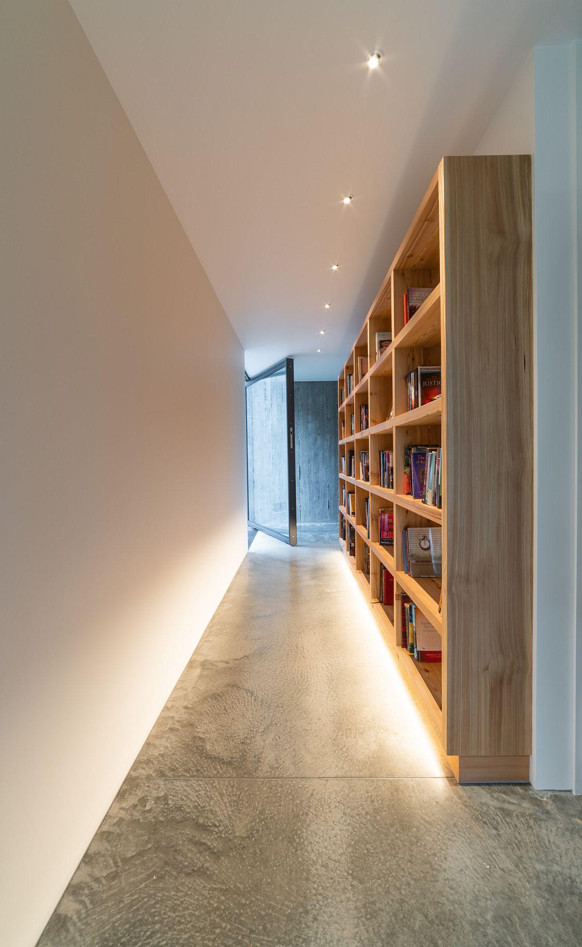 Giá sách gỗ tùy chỉnh ở hành lang thêm một cái gì đó khác biệt cho ngôi nhà hiện đại.