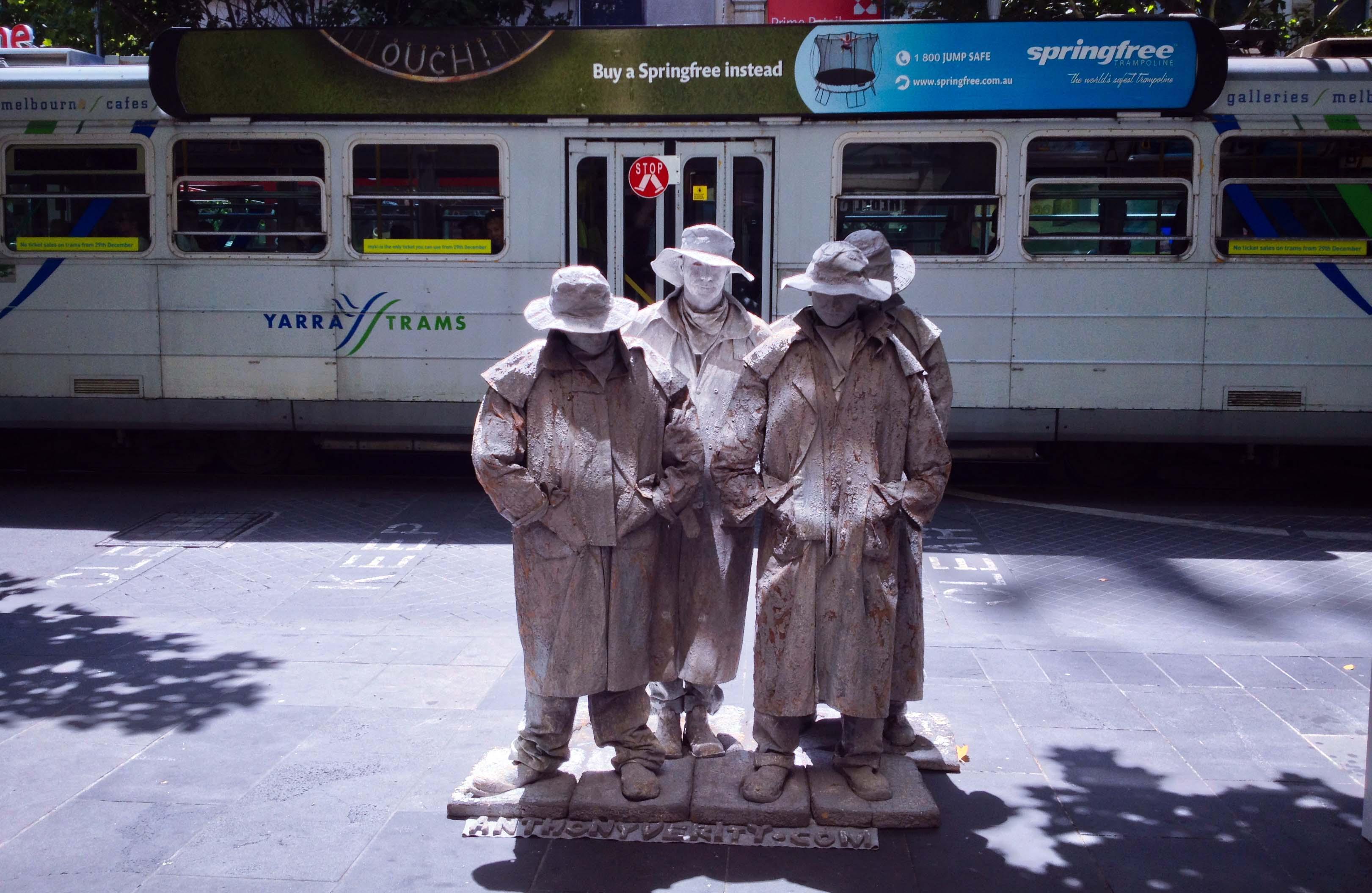Bốn người tượng đứng trước trạm tàu điện (tram) trong một trưa hè tràn nắng trên khu phố mua sắm Bourke Street Mall. Họ đứng bất động hàng giờ, mỗi tư thế thay đổi đều giữ rất lâu.