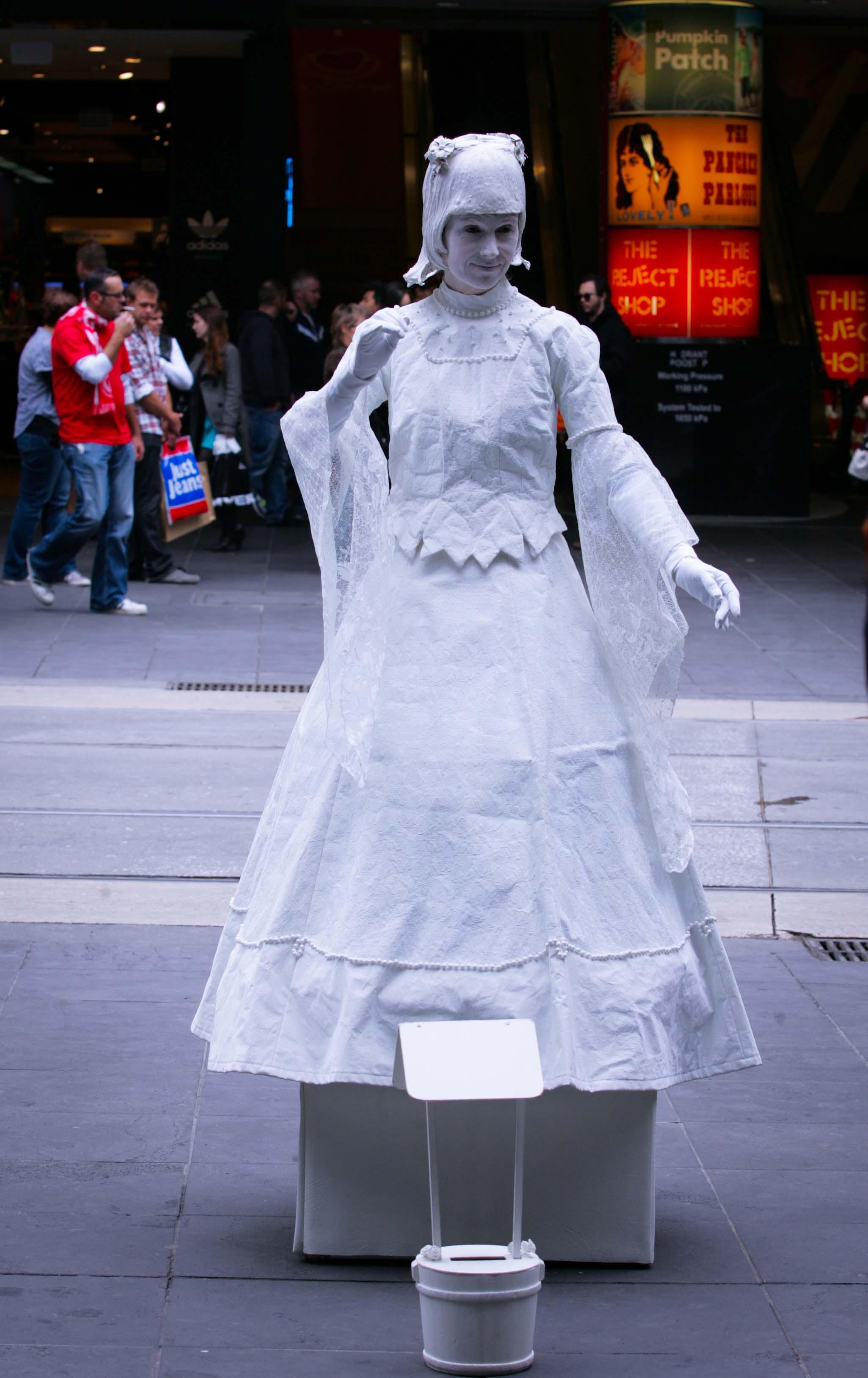Trong khi một quý cô gần đó lại mặc váy dài, cuốn tóc như thế kỷ 18 - 19 đang cử động chậm rãi như thước phim cũ quay chậm. Dưới chân, một chiếc xô nhỏ để du khách đi qua thả vào đó những đồng xu.
