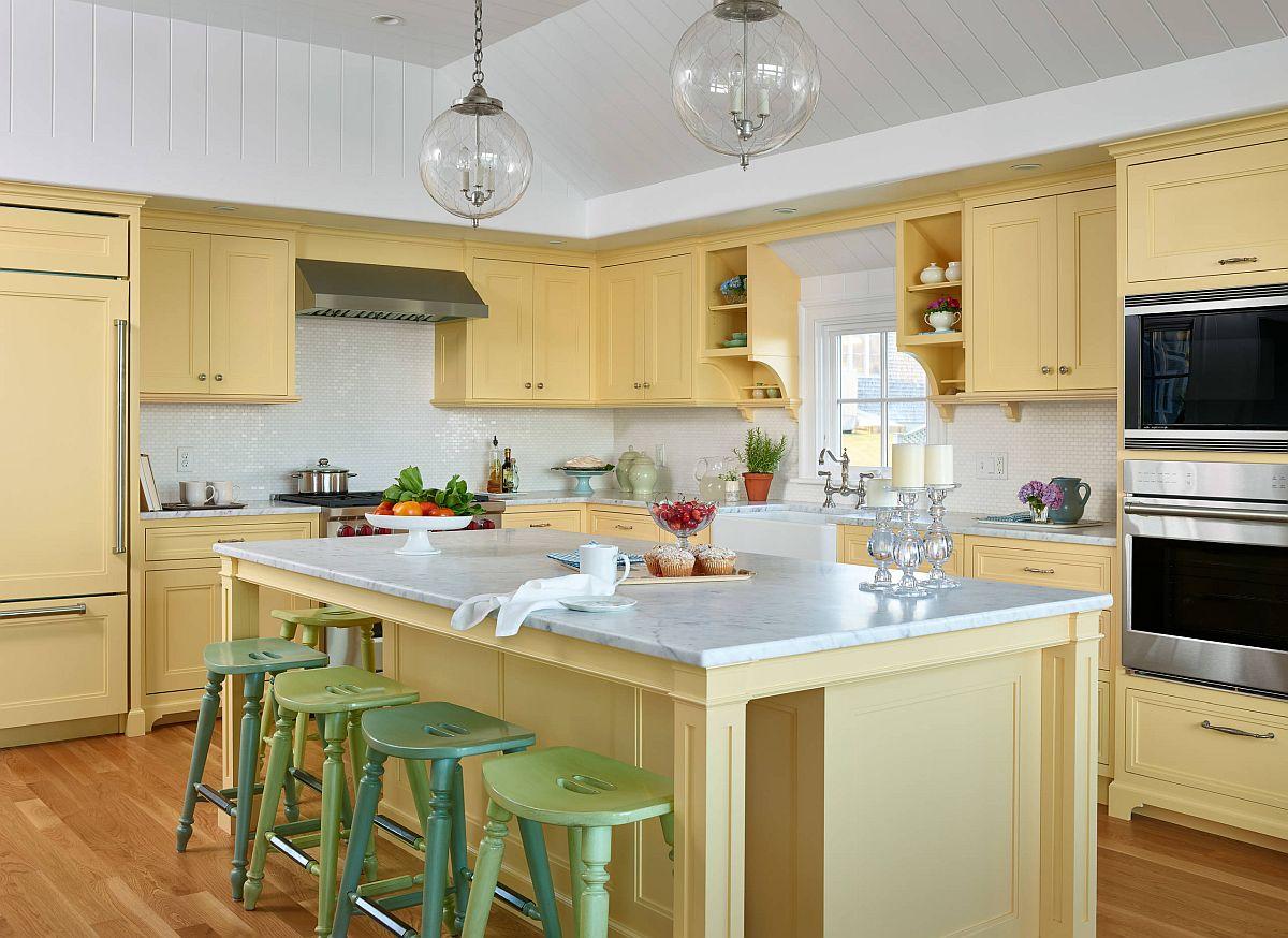 Phòng bếp phong cách biển tươi vui và nhẹ nhàng được tạo nên từ tone màu vàng nhạt và những chiếc ghế đẩu màu xanh lá pastel ở đảo bếp.