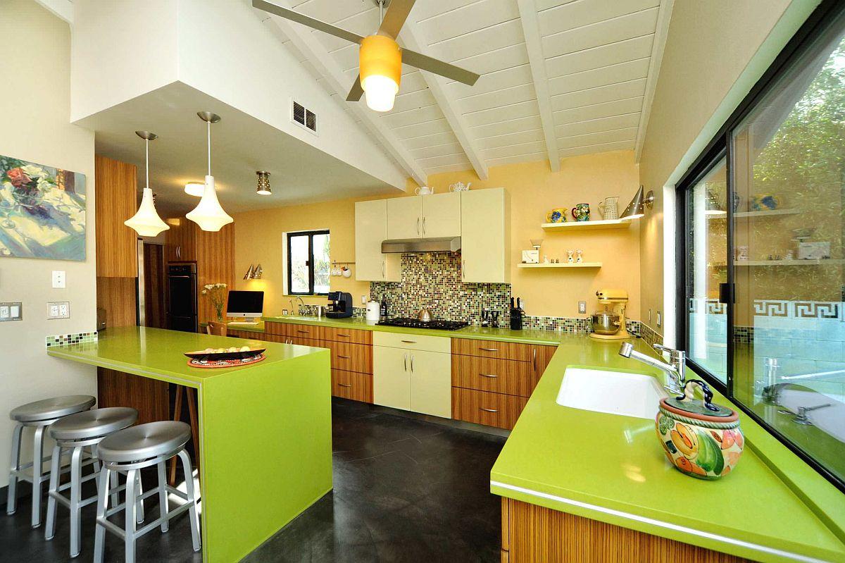 Nhà bếp hiện đại theo phong cách mid-century tuyệt đẹp với bức tường tạo điểm nhấn màu vàng và mặt bàn màu xanh lá cây bắt mắt.